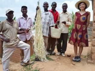 ラフィア椰子の葉で編んだバッグを持って笑顔を見せるブルンジの職人たちとドゥサベ友香さん(右)