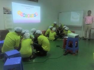 カンボジアの経済特区にある工場で、RIC(報・連・相)研修の一環として「輪っかゲーム」に真剣に取り組む参加者たち