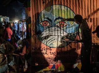 ケニアのアーティスト、グランドサンさんがナイロビのキベラ地区で描いたグラフィティ。地球がマスクを被っている。新型コロナウイルス感染症の予防意識を高めることが目的だ。2020年3月23日に撮影(Yasuyoshi CHIBA / AFP)