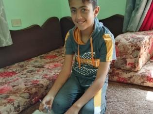 シリア難民のバーゼルくん。オンラインの補習授業を受けて、笑顔を見せる(写真提供:ワールド・ビジョン・ジャパン)