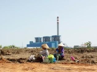 インドネシア西ジャワ州のムカリサリ村の発電所建設予定地の前でたたずむ小作農