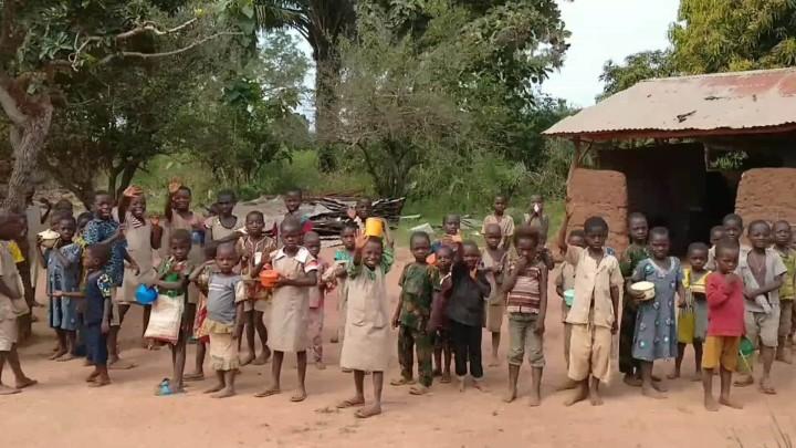 コベ村の小学校の子どもたち。右奥に写るのが泥と木、トタンで造った校舎