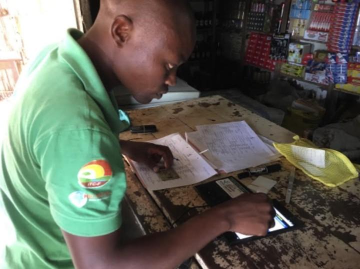 キオスクの端末を操作するレジ係。モザンビークの農村では大雨が降るたびに通信施設が壊れる。復旧に1~2週間かかることも。このためスマートフォンに依存するシステムだと、インターネット通信が切れた場合に電子マネーが使えなくなる(写真提供:日本植物燃料)