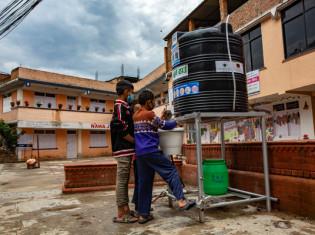 ネパール・キルティプルのバス停にウォーターエイドが設置した手洗い設備で手を洗う地元の子どもたち。足元のペダルを踏むと水とせっけんが出る。蛇口を触らなくて済む(WaterAid/ Mani Karmacharya)