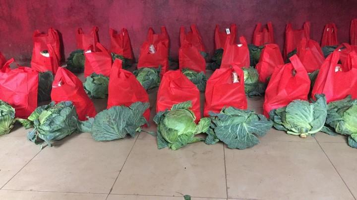 A-GOALプロジェクトで配るキャベツとその他の食料が入った赤い袋