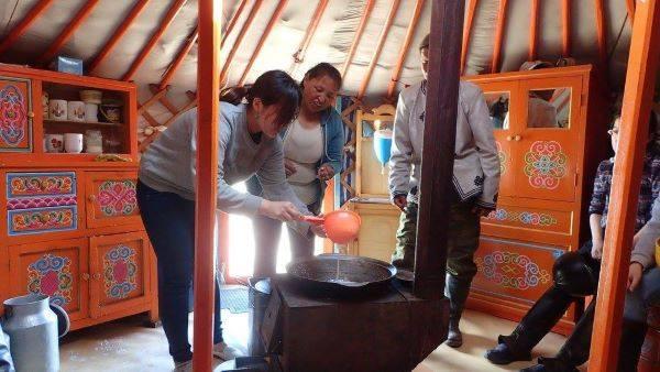 ゲルの中で自家製ヨーグルトづくりを体験する観光客。鍋、ストーブ、搾りたての牛乳、少しのヨーグルトがあれば、機械なしでも簡単にヨーグルトは作れる