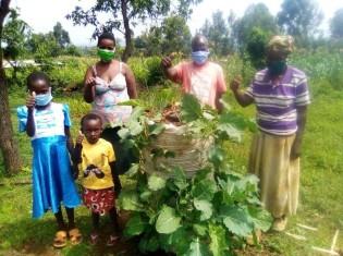 マルチストーリー菜園の収穫をする保健ボランティア(男性)と住民ら
