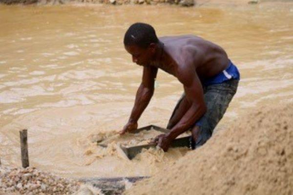リベリア西部のバポル州ウィズア村で働くダイヤモンド採掘労働者。川の土砂を大きな器ですくい、ダイヤの原石を探す(ダイヤモンド・フォー・ピース提供)