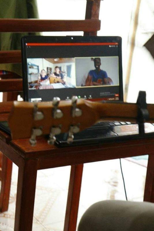 ギターのオンラインレッスンをしているところ。講師は指の動きをカメラに映して弾き方を指導する。世界9カ国から生徒がレッスンを受ける