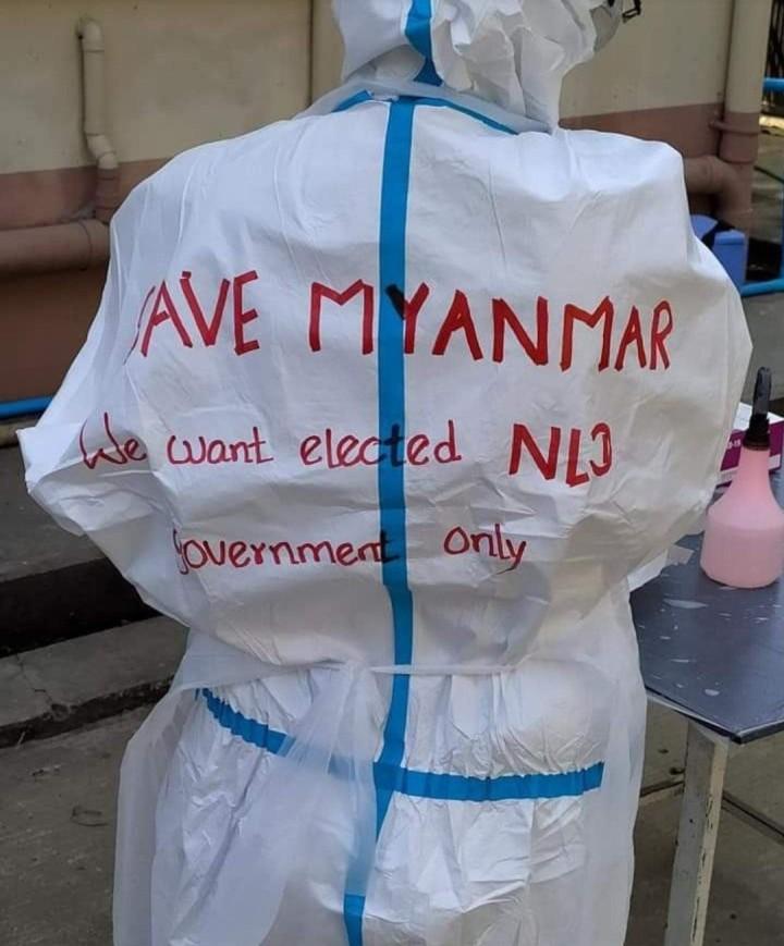 職務をボイコットしていない医療者も、防護服にメッセージを書いて、不服従の意志を示す。背中に書かれたメッセージは「ミャンマーを守ろう。私たちが認めるのは、選挙で選ばれたNLD政権だけ」。画像はフェイスブック(#Civil Disobedience)から引用