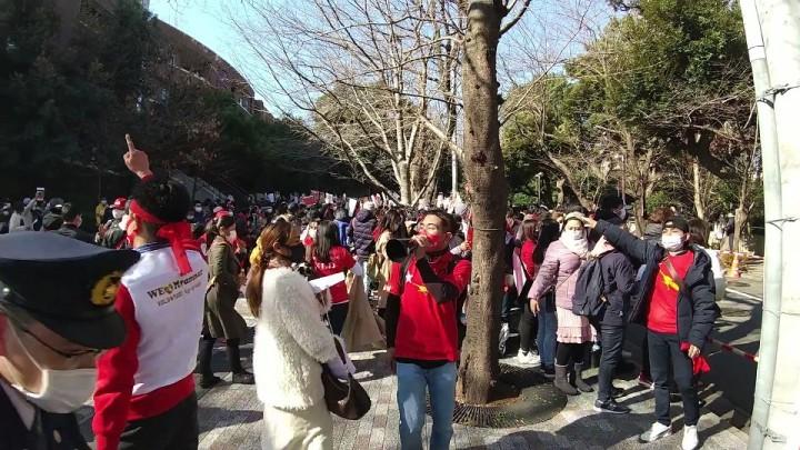 「We♡Myanmar」の白いベストを着た男性、赤いNLDのTシャツを着たボランティアスタッフたち。拡声器などを使ってデモの参加者を車道にはみ出ないよう誘導する