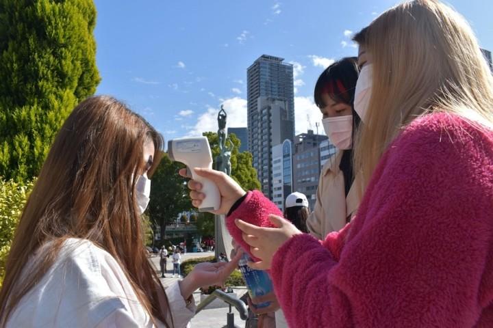 新型コロナウイルス感染予防対策で、抗議集会の参加者は検温と手指の消毒をする