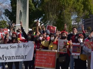 中之島公園に集まった抗議集会の参加者ら。手にする花束には「平和」の意味が込められている