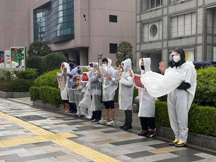 ミャンマーの現状を知ってもらうために雨の中、通行人に声かけをするハンガーストライキの参加者たち(東京・渋谷の国連大学前)