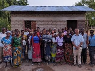 教室建設の足がかりとして2020年5月、マラウイ南部のパロンベ県にある13の小学校で倉庫を建て終えた。完成した1つの倉庫の前で記念撮影する、建設作業に参加した小学生の保護者とCanDoの永岡代表理事(前列右)。永岡氏を含む日本人スタッフ3人は、新型コロナウイルスの影響で2020年4月に緊急帰国して以来、リモートでプロジェクトを進める