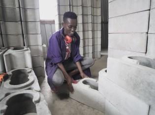 「角度を自由に変えられる」とツイストブロックの使い方を説明するアチエンさん(ナイロビ・キベラスラム)
